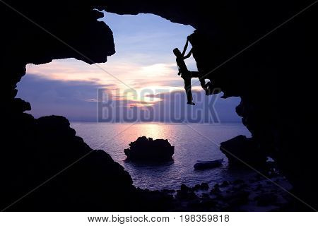 Photographer climbing rock in the cave near the beach with kayaking and purple sky sunset.