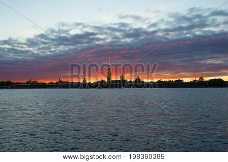 Panorama of the Peter and Paul fortress against the backdrop of a gloomy sunset. Saint-Petersburg, Russia