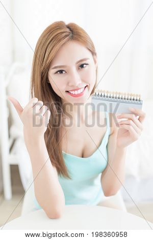 woman with tooth color palette at home