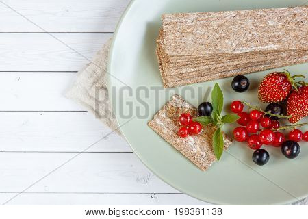 Healthy Snack from Wholegrain Rye Crispbread Crackers and Fresh berries on the Light Background.
