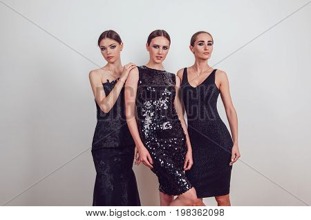 Attractive girls in black cocktail dresses on a grey background.