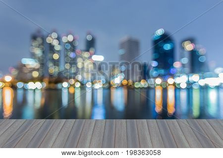 Opening wooden floor city office building blurred bokeh light with reflection night view abstract background