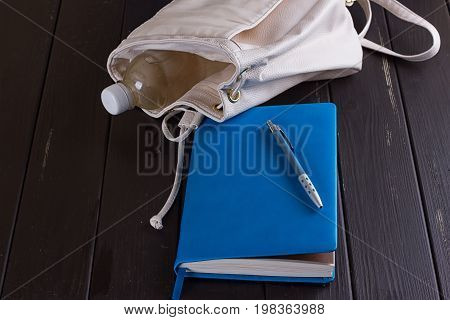 White leather backpack blue notebook and pen on a black wooden background