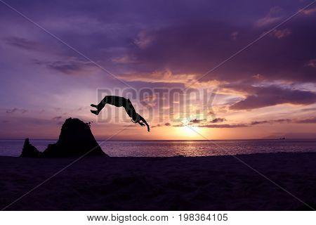 Asian girls somersault on the beach with purple sky sunrise.