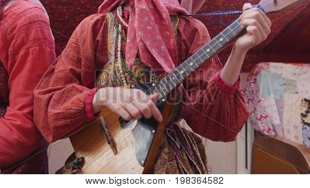 Folk music russian ensemble - woman in Russian folk costume playing the balalaika, close up