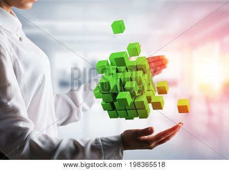 Cropped image of business woman hands holding multiple green cubes in hands with sunlight on office background.