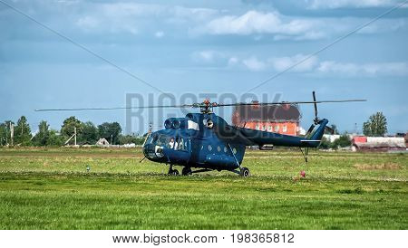 Blue helicopter on the pad produces a take-off. The horizontal frame.