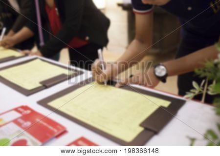 Blur Image of People registration form on meeting room