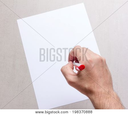 male hand with a ballpoint pen and a blank white sheet of paper on grey background top view closeup. mock up for text congratulations phrases lettering