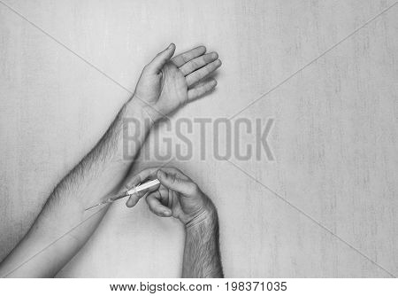 The hands of the man making himself an injection of a disposable medical syringe on a gray background with space for text. black and white photo