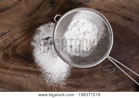 Wheat flour in sieve for sifting on wooden background,food ingredient for bread or cake