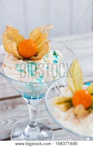 Eton mess in martini glass with syrup and ripe physalis.