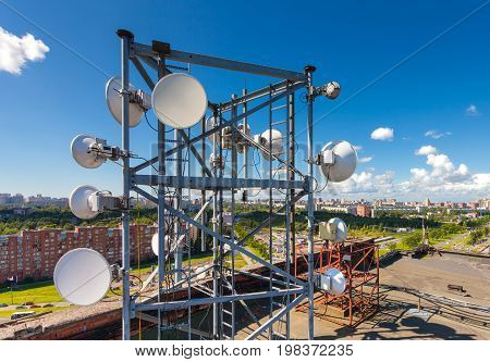 Telecommunication tower with TV antennas satellite dish microwave and panel antennas of mobile operators is located on the roof and city landscape as background
