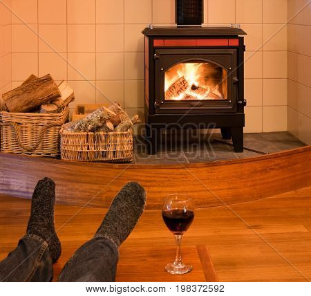 Feet with socks of a single man relaxing by fire in woodburning stove with glass of red wine - focus is on stove
