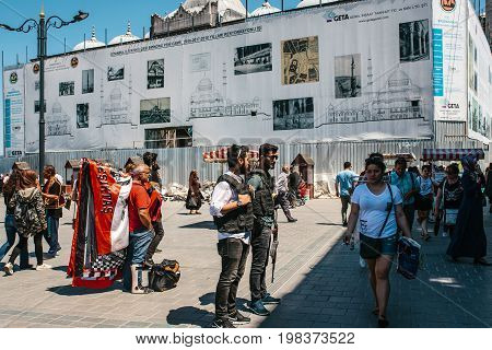 Editorial image of people at Eminonu Square in the middle of the day - police officers, man with medical cast on his leg, casually dressed woman in white t-shirt and random passerby.