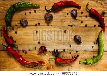 Chili garlic rosemary pepper on a wooden surface top view