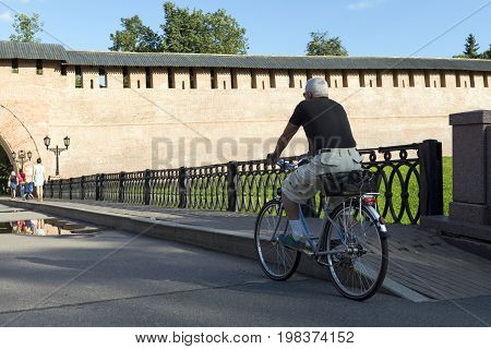 gray-haired man in shorts riding a Bicycle across the bridge on the paved road towards the terracotta fortress wall of the Novgorod Kremlin the asphalt people walking