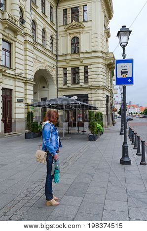 VILNIUS LITHUANIA - JULY 10 2015: Unknown girl stands at taxi stop near Lithuanian National Philharmonic in Old Town Vilnius Lithuania