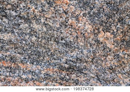 Background of granite stone close-up. On gray background there are inclusions of pink mineral.