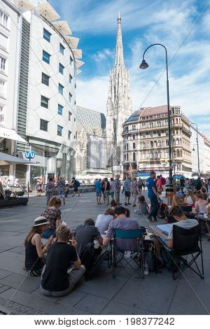 Vienna Austria - July 31 2017: Stephansplatz in Central Vienna with famous St. Stephens Cathedral. Students sitting on the street and drawing the church.