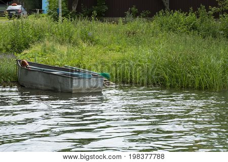 old small boat with oars is docked on the shore of the river the grass water countryside