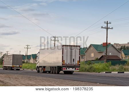 Two White Lorry With White Trailer Over Blue Sky On The Road