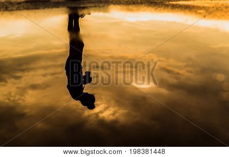 Photographer silhouette refection with yellow sky .