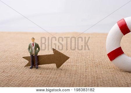 Man Figurine Led By An Arrow To Life Preserver