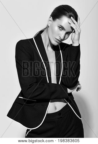 Fashion style model in black suit posing in the studio white background black and white