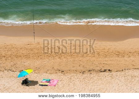 Summer view from above of sun parasols and a fishing rod on a sunny beach in Portugal.