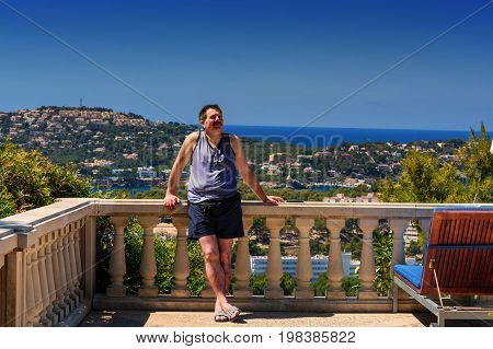 Man is relaxing on a balcony overlooking the sea.