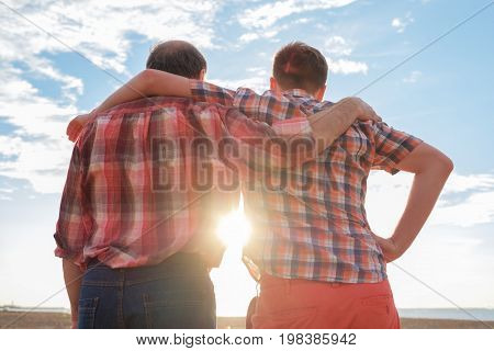 adult father and son holding hands at sunset. Good relationships between generations