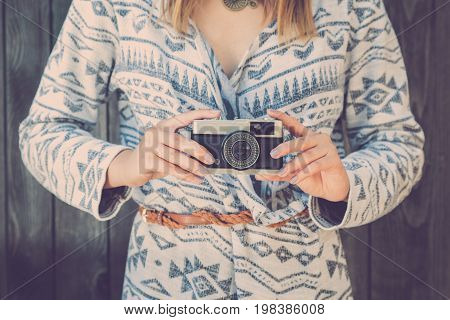 Close up of fashionable retro styled female holding vintage old film camera