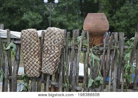 Old shoes hang on the fence and dried. Russian retro shoes.