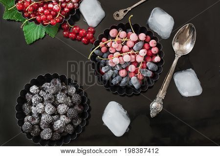 Frozen red currant, black raspberries garnish of ice, branch red currant in dark plate on a black background.