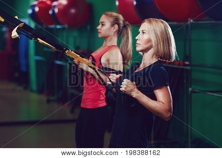 Beautiful young sports people are working out with TRX in gym
