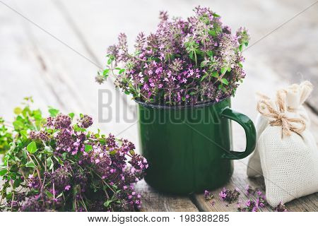 Enameled mug full of thyme flowers on white background. Herbal medicine.