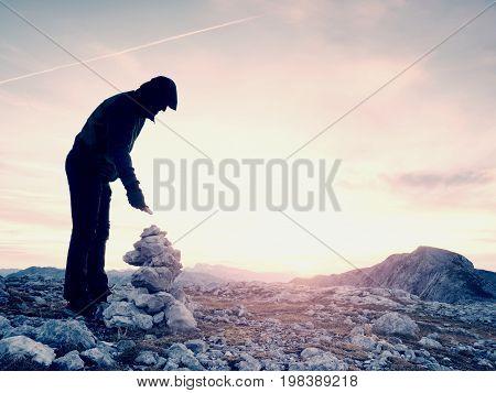 Man Put The Last Stone Intopeak Of  Pyramid. Balanced Stone Pyramid On  Mountain Summit.