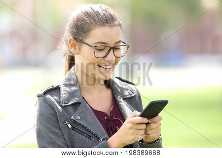 Portrait of a single happy girl wearing eyeglasses texting in a mobile phone walking in a park outdoors
