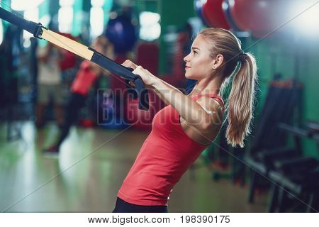 concentrated sportswoman training with resistance band in sports center