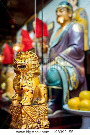 Shanghai, China - Nov 6, 2016: In the 600-year-old Old City God Temple. A small decorative wooden lion painted in gold on railing post. Low-light image with shallow depth-of-field.