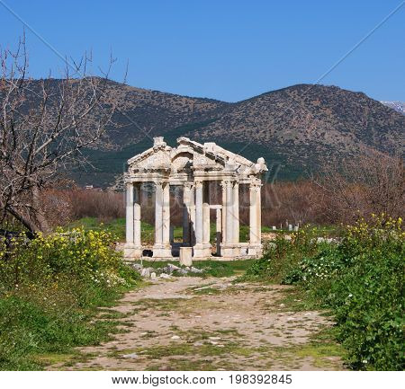 Ruins of a small ancient greek temple in south Turkey on a background of mountains among green mealow with a way leads to the temple. The ruins consits of colonnade and two Tympanums build from white stones.
