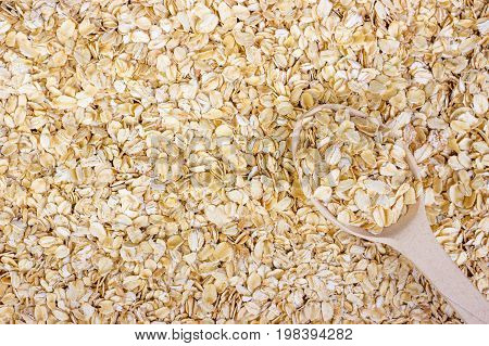 pile of oat flakes and wooden spoon on oat flakes background