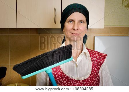 Portrait Of Woman With A Broom In The Kitchen
