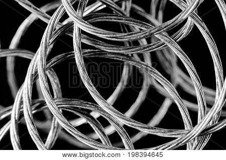 Entangled silver cable wire on a black background