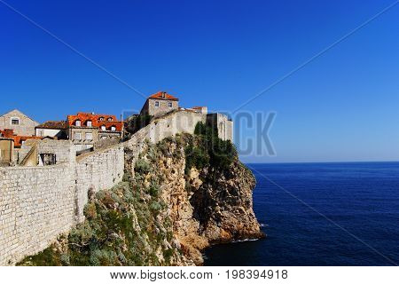 white stone wall of the old town of dubrovnik on a rock on the background of a blue and empty sky and blue water of Adriatic sea. Behind the wall old houses with red roofs.
