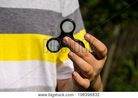Boy Playing With Fidget Spinner Stress Relieving Toy Outdoor
