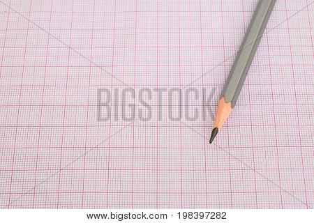 closeup of pencil on red graph paper (grids)