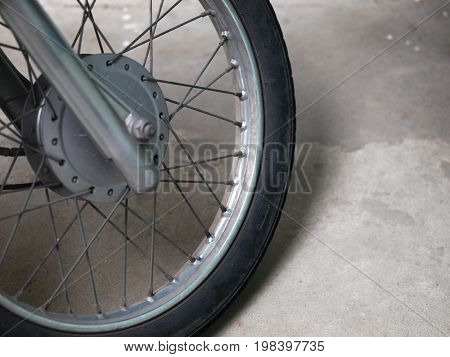 COLOR PHOTO OF CLOSE-UP OF MOTORCYCLE SPOKES AND WHEEL