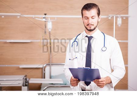 Doctor holding a folder in hands with stethoscope arround his neck in hospital recovery room. Medicine and healthcare